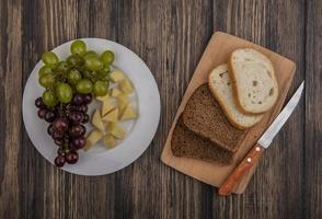 Sliced bread and fruit on wooden background