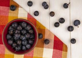 Dark berries and plaid cloth on a white wooden background
