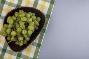 Uvas blancas en un recipiente sobre tela escocesa sobre fondo gris foto