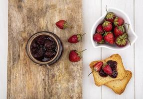 Berry toast and jam on a white wooden background