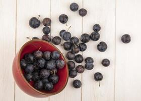 Dark berries in a red bowl on a white wooden background