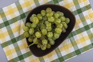 Uvas blancas en un recipiente sobre tela escocesa sobre fondo gris