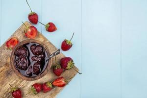 Mermelada de fresa con fresas frescas sobre un fondo azul.