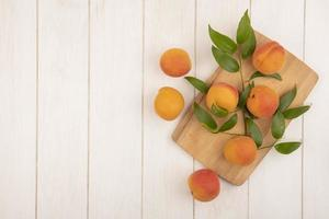 Apricots and leaves on cutting board on wooden background