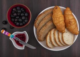 rebanadas de pan y fruta sobre fondo de madera foto