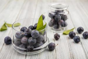 Dark berries in a glass jar with leaves