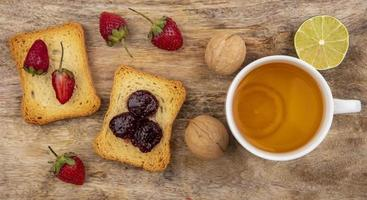 Toast with fruit and tea on a wooden background