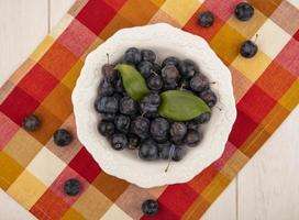 Dark berries on plaid tablecloth background photo