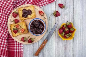 Strawberry toast and jam on gray wooden background