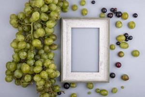 Assorted grapes and wooden frame on gray background with copy space