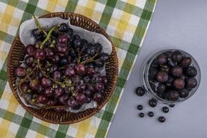 Grapes on plaid cloth on gray background