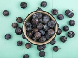 Dark berries on a blue background with copy space photo
