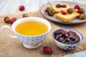 Tea and jam with toast on wooden background