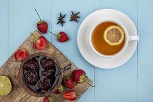 mermelada de té y bayas sobre un fondo azul foto