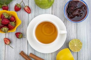 Tea and fruit on gray wooden background