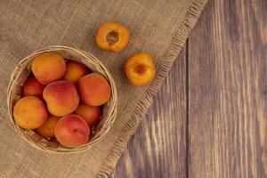 Apricots on a sackcloth on wooden background