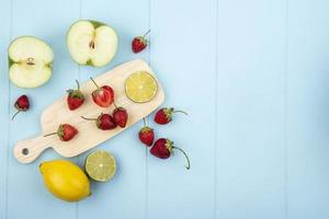 Fruta variada sobre un fondo azul con espacio de copia foto