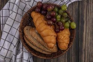 Bread and fruit on plaid cloth on wooden background photo