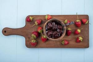 Strawberries and jam on wooden blue background