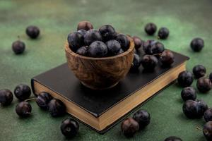 Dark berries in a wooden bowl on green background