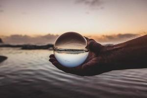 Person holding a glass ball
