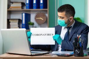 joven empresario con cartel de coronavirus