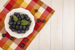 Dark berries on a checkered tablecloth background