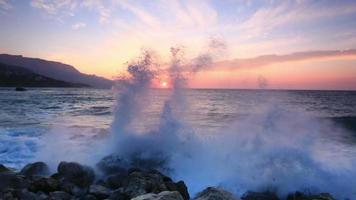 Big waves break about stones at sunrise