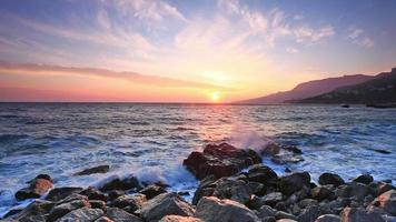 havsvågor bryter om stora stenar nära stranden