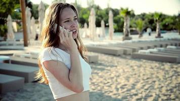 jovem falando na praia do telefone móvel nas férias de verão.