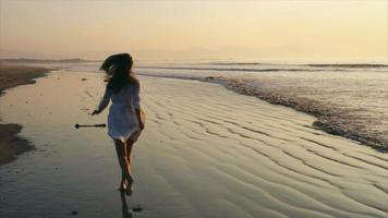 Slow motion of happy woman running on wet shore during sunset