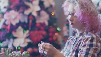 chica hipster haciendo adornos navideños