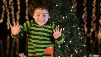 criança linda dançando animadamente em frente à árvore de natal