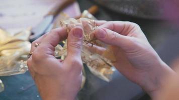 weibliche Hand gebunden Bogen des Goldbandes, um den Weihnachtsbaum zu schmücken