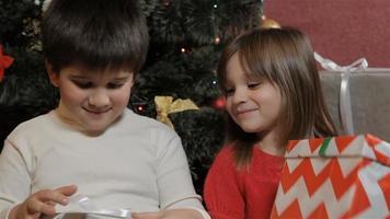 los niños miran sus regalos de navidad