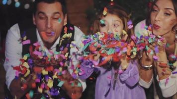 Happy family celebrating Christmas and New Year by blowing colorful confetti