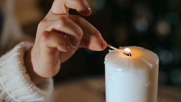 mujer joven encendiendo una vela de navidad