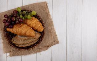 Bread and fruit on wooden background with copy space photo