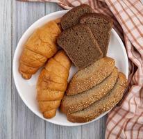 Rebanadas de pan sobre tela escocesa sobre fondo de madera foto