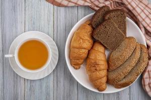 Rebanadas de pan y té sobre fondo de madera