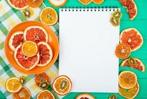 Vista superior de un cuaderno de bocetos con naranjas secas