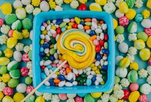 Top view of colorful lollipop on candies in multi-colored glaze background