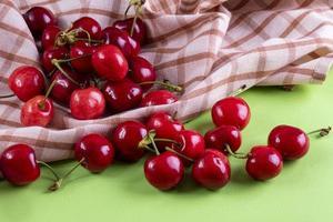 Vista frontal de cerezas rojas con un paño de cocina sobre un fondo verde claro