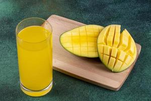 Side view of sliced mango and juice