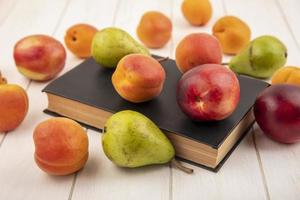Side view of fruits on closed book and on wooden background