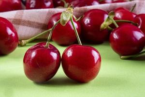 Front view of red cherries with a kitchen towel on a light green background