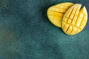 Top view of sliced mango on a green background
