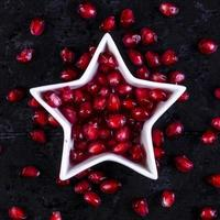 Top view peeled pomegranate in the shape of a star on a black background