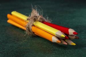 Side view of colored pencils tied with a rope
