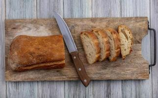 Vista superior de pan crujiente en rodajas y cuchillo